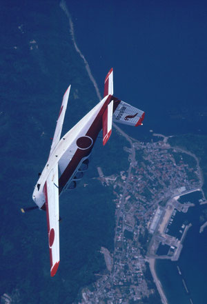 A JASDF cadet in a T-3 primary trainer does a loop over a coastal fishing town.