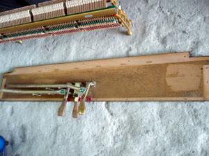 ピアノを解体していきます。外されたアクションと、ペダルが付いている底板です。