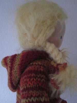 ... mit goldblonden Zöpfen und einer hübschen Kapuzenstrickejacke aus rot-orange-gelber Finhofwolle...