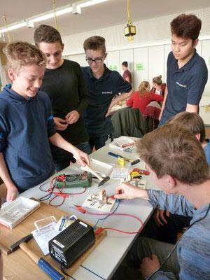 Auszubildende bei Ziehl-Abegg, bauen mit Neuntklässlern an der Realschule Krautheim Elektromotoren.