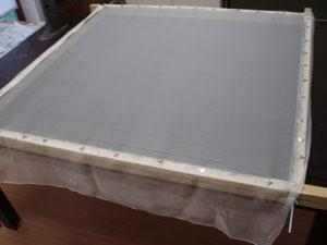 la soie est tendue sur le cadre avec des punaises