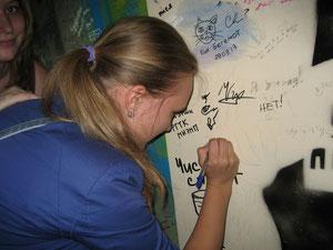 Катя Латышева пишет на стене подъезда