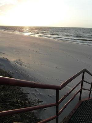 Zejście na plażę w Ustce w promieniach zachodzącego słońca.