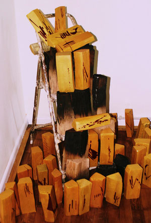 Installation Asche-Gold, Holzscheite mit Goldüberzug und roten Zeichen, Holzscheite mit Feuer bearbeitet