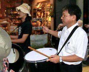 太鼓をたたく石原市議(右側)
