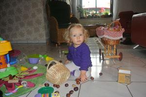 Alina spielt mit Kastanien