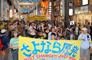 「さよなら原発」と書かれた横断幕を掲げ、アーケード街を行進する市民ら=11日午後3時すぎ、熊本市