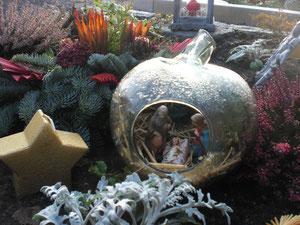 """Alte Krippenfiguren in einem """"Glasapfel"""" auf einem Grab. Der Apfel erinnert an Eva und die Paradiesgeschichte."""