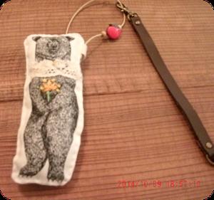 クマの柄の生地で作ったマスコットに、刺繍、レース、ビーズなどで飾り、りんごのボタンとレザーでストラップを付けてみました。