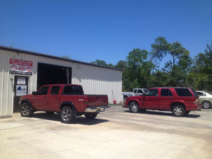 Red pickup truck and SUV parked in front of Auto Squad repair facility in St. Augustine, Florida.