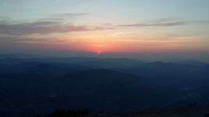"""L'astre du jour pointe son """"nez"""" derrière les sommets Alpins"""