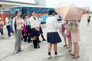 「ニーハオ」。ちょっぴり照れながらも台湾観光客に話しかける八商工の3年生=石垣港
