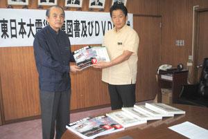 東日本大震災関連の書籍を中山市長に手渡す桃原さん=22日午前、市役所