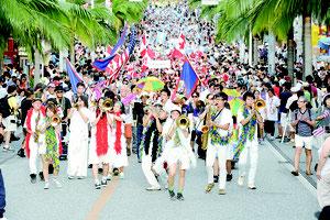 音楽隊が聖者の行進を演奏しパレードするニューオリンズの県系人ら=26日午後、那覇市の国際通り