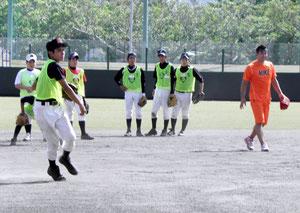 黒木さん(右側)から、守備の指導を受ける中学生=市中央運動公園野球場