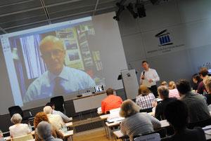 Dr. Rieger moderiert einen Vortrag von Dr. Mark Thompson