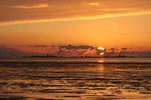 Bild:Sonnenuntergang im Watt vor Duhnen über der Insel Neuwerk, Vom Balkon einer Ferienwohnung