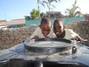 Sarah und Anna freut es, dass sich der Tank mit Wasser fuellt.
