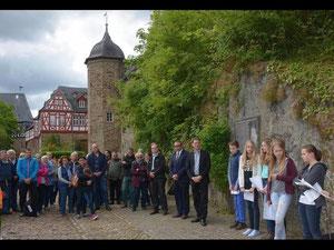 Vor der Gedenktafel (rechts an der Mauer) werden die Namen der im Hexenwahn in Idstein Getöteten verlesen. Foto: Stefan Gärth