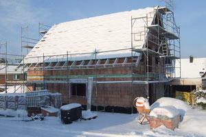 Der Schnee liegt AUF dem Haus, nicht IM Haus
