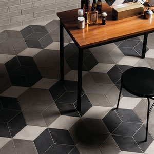 A floor with black, gray, and white rhombus tiles set in an unusual pattern.