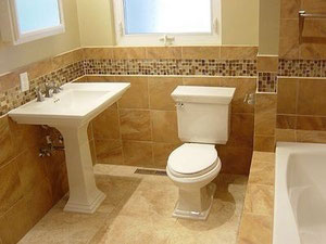 Travertine bathroom with wainscoting and a glass mosaic border