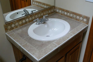 Brown bathroom vanity with travertine backsplash