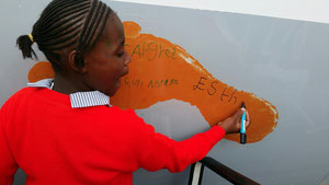 Twelve-year old Esther Waithera of Mothers' Mercy Home is writing her name on the hull of the MD-11F
