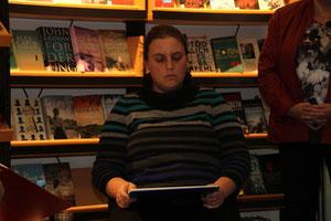 Lesung vor einem vollen Bücherregal. (c) Norbert Spitzner