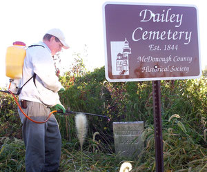 WIU Professor Tom Green clears the Dailey Cemetery for its new sign donated by the McDonough County Historical Society.