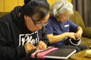 ステーシー・スカンとアンナ・フリスビーが毛糸のヘッドバンドにラッコの毛皮を縫い付けている。ハイダバーグの職人協同組合へ寄付する。