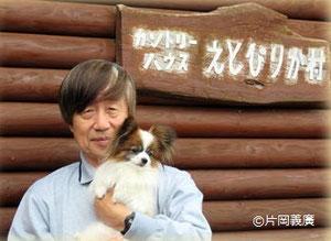 特定非営利活動法人エトピリカ基金理事長の片岡義廣さん。愛犬のモンザブローとゲストハウス「えとぴりか村」の前で。