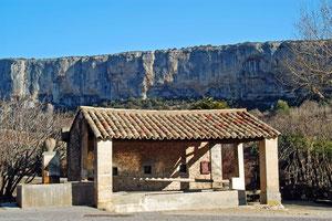 Lavoir du village de Lioux, en fond la falaise de Lioux