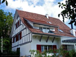 Fitze Dach AG Steildach mit Lukarne an einem schönen Riegelhaus, mit Biberschwanzziegeln bedeckt.
