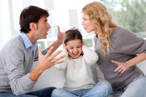 Streitendes Paar, dazwischen ein Kind, das sich die Ohren zuhält.