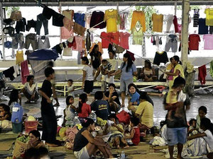 A DAY IN THE LIFE. After the laundry is done, evacuees attend to their routinary household chores at Manggahan covered court in Rodriguez, Rizal. ARNOLD ALMACEN