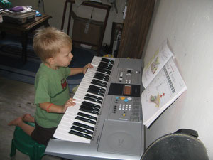 Caleb experimenting with our new keyboard that we use for music lessons.