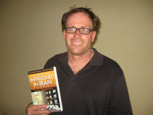 Dan with his book about his experience in an Iranian prison