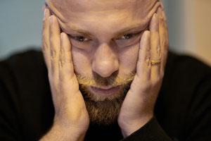 Ein Mann stützt seinen Kopf resigniert und depressiv zwischen beiden Händen.