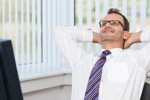 Ein Mann mit weißem Hemd und Krawatte lehnt sich relaxt und angstfrei am Schreibtisch in seinen Schreibtischstuhl zurück, die Arme sind hinter dem Kopf verschränkt.