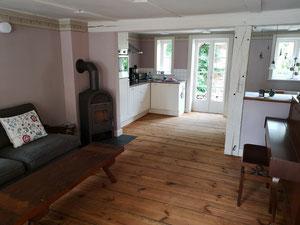Wohnzimmer mit Kamin und Klavier sowie Küche mit Blick in den Garten