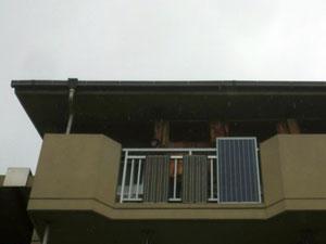ベランダに垂直に設置された3枚の太陽光パネル。作った電気はパソコン、プリンター、CDプレーヤー、照明、扇風機などに使用