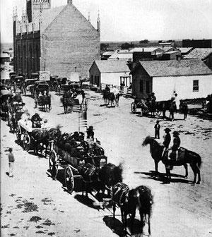Indianerhäuptlinge fahren 1864 zu Friedensverhandlungen in Denver ein. Trotz monatelanger Indianerüberfälle in diesem Gebiet kamen viele Bürger zur Begrüßung aus ihren Häusern. Das war zwei Monate vor dem Massaker am Sand Creek.