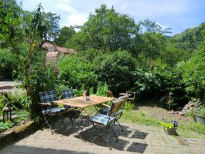 Foto zeigt Terrasse und Garten vor der Ferienwohnung, einen Sitzplatz, gemauerten Ofen, Föhrlenberg im Hintergrund