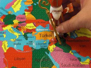 Eine Nikolaus•figur steht auf einer Landkarte.