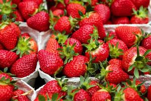 Hier zu sehen: Erdbeeren in Schalen auf einem Marktstand.
