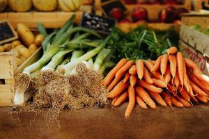 Hier sehen sie Karotten und Poree und Kartoffeln auf einem Marktstand.