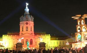 Weihnachtsmarkt vor dem Schloss Charlottenburg, das Schloss in orangem und gelbem Licht. Foto: Helga Karl 2014