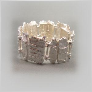 Schweres Armband in Silber. Die verschieden groß gearbeiteten Glieder haben eine kräftige Oberflächenstruktur.