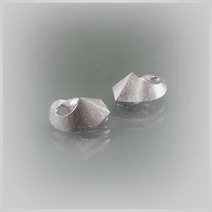Ohrclipse in Silber mit schraffierter Struktur, die organische Rundung schmiegt sich an das Ohrläppchen an.